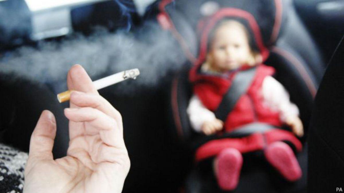 Un fumador con un niño en el coche