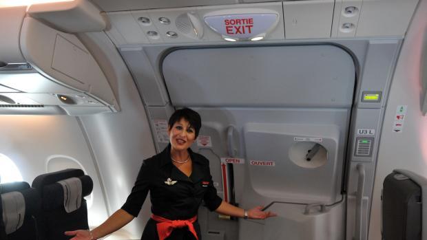 Una azafata en la puerta de un avión