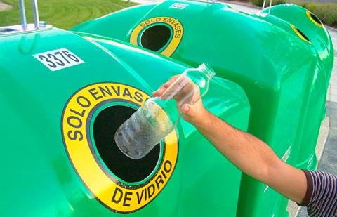 Reciclando una botella en un contenedor de reciclaje de vidrio