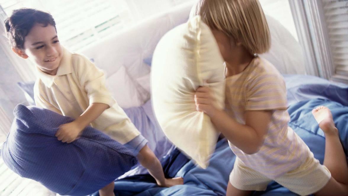 Dos niños jugando con almohadas