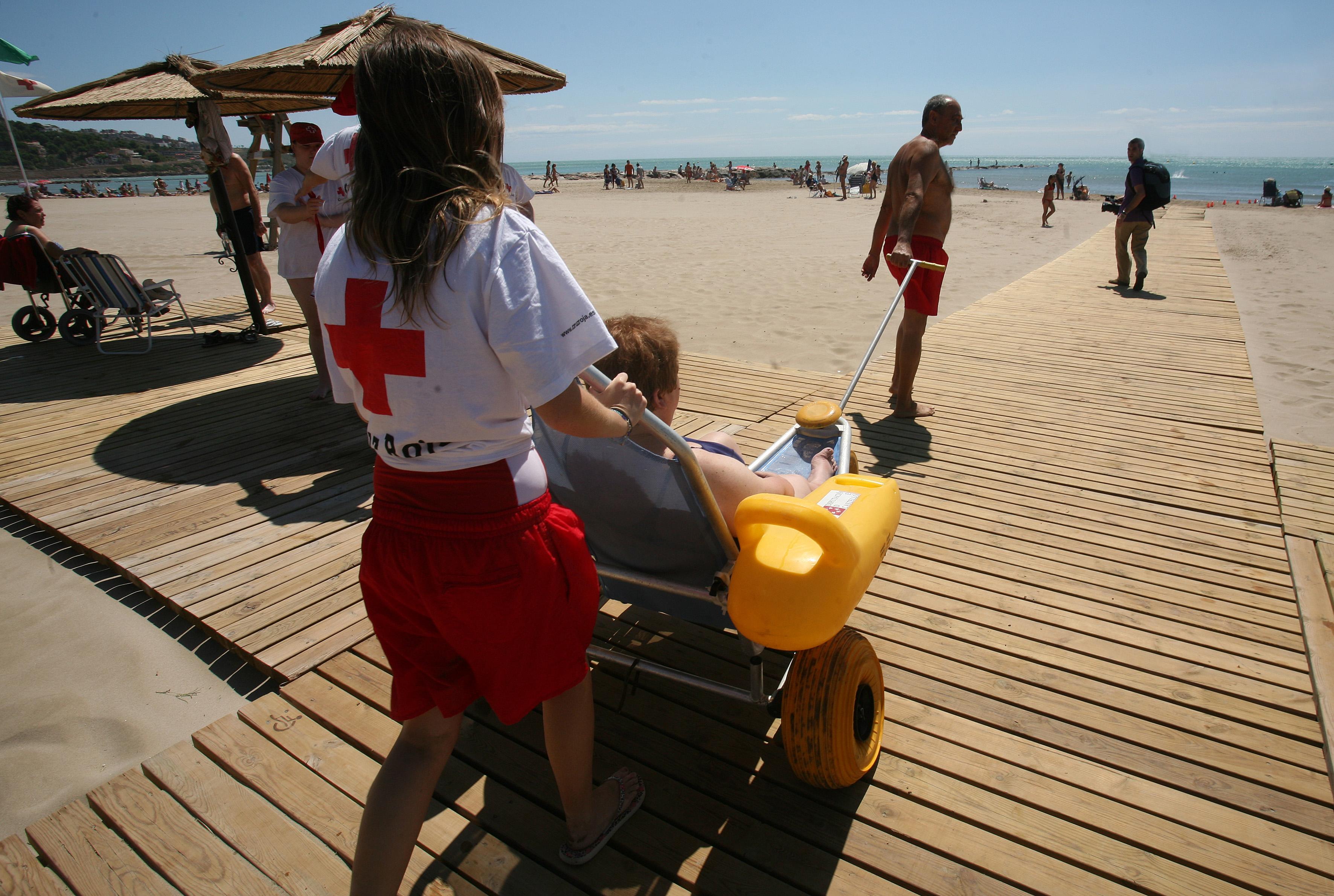 Una chica de la Cruz Roja con una silla accesible para el baño en una playa