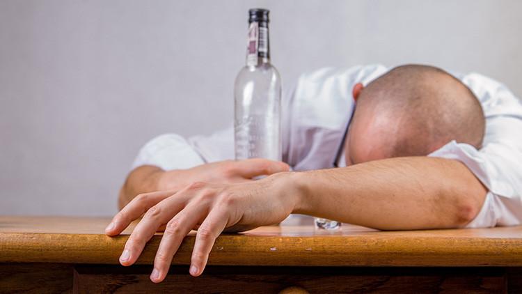 Un hombre dormido con una botella de alcohol