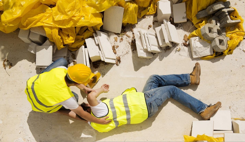 Un obrero de la construcción caído y otro ayudándole
