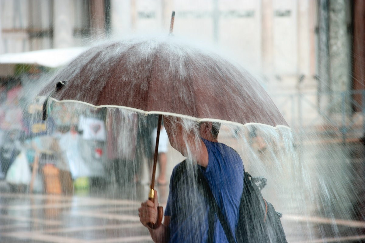 Una mujer con un paraguas caminando por la calle