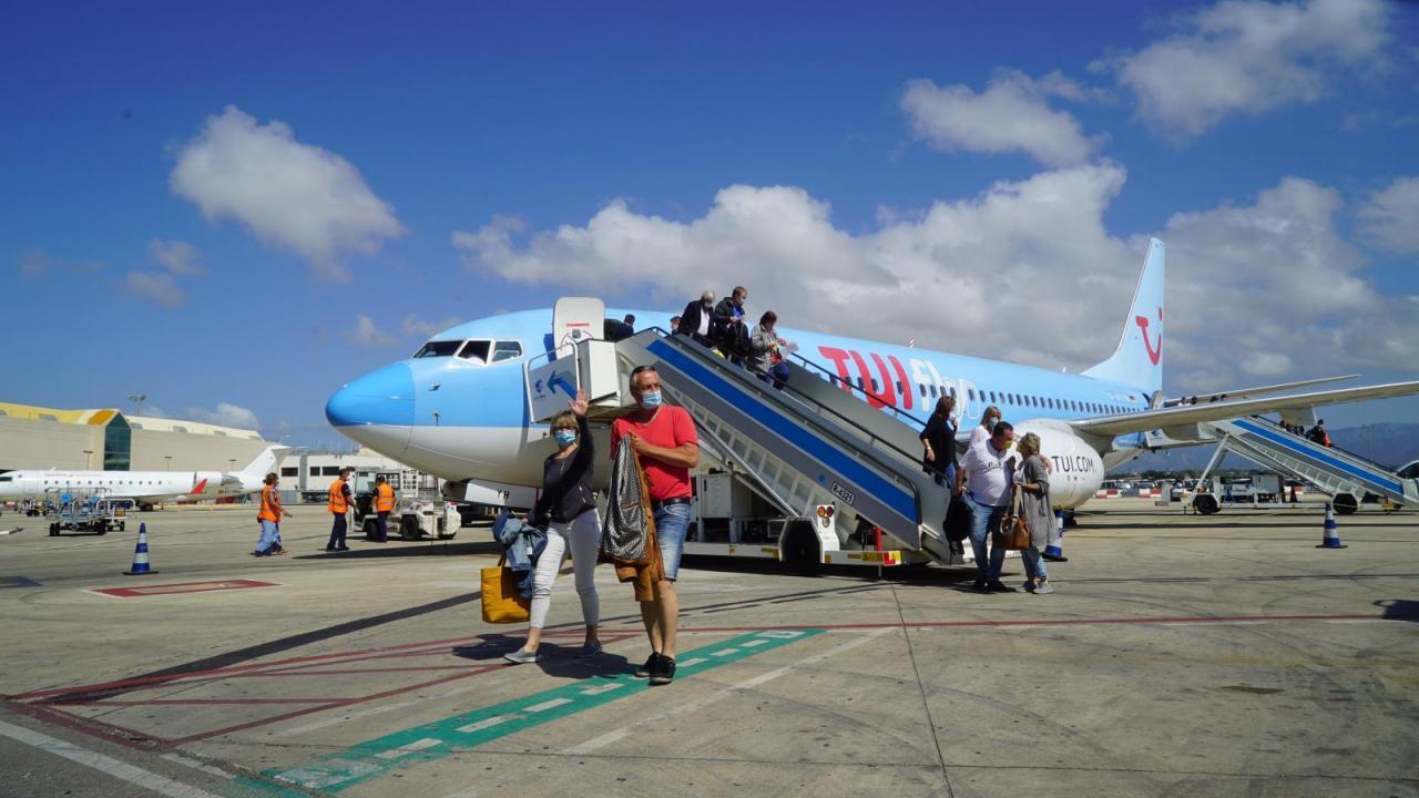 Turistas bajando de un avión del grupo turístico alemán TUI