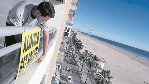 """Un hombre poniendo un letrero de """"Se Alquila"""" en una vivienda"""