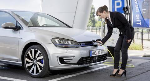Una mujer cargando un coche eléctrico