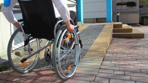 Una persona en silla de ruedas subiendo una rampa