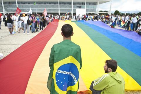 Un hombre con una bandera de Brasil y bandera LGTB