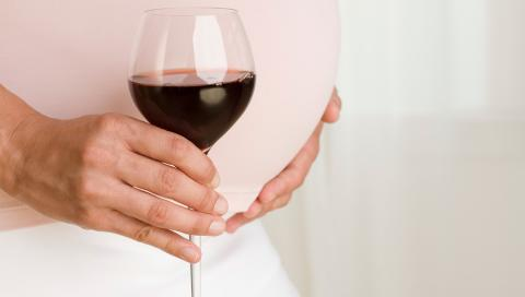 Una mujer embarazada con una copa de vino