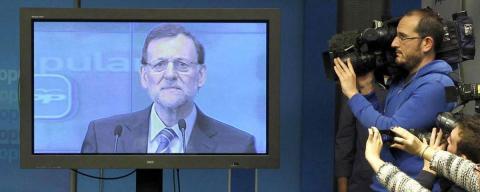 Mariano Rajoy en un televisor y varios periodistas