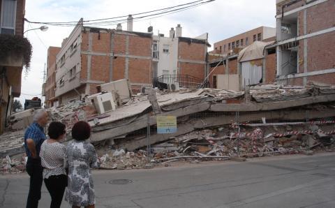 Unas personas viendo un edificio destruido después del terremoto de Lorca