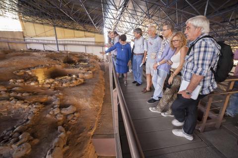 Un grupo de visitantes en el yacimiento arqueológico de la Cueva Pintada