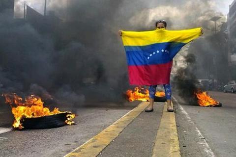 Una persona con la bandera de Venezuela en una manifestación