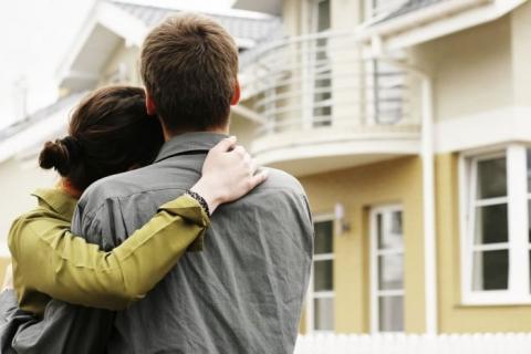 Pareja de jóvenes frente a una casa