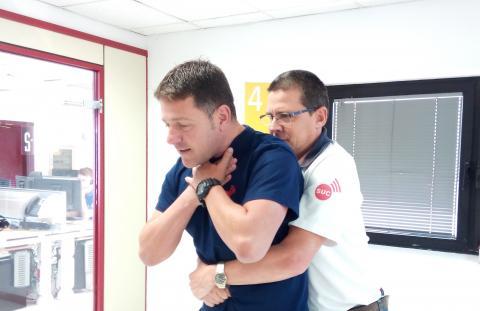 Dos hombres practicando la maniobra de Heimlich