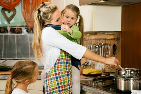Una mujer cocinando y con niños