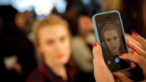 Fotografiando a una persona con el teléfono móvil