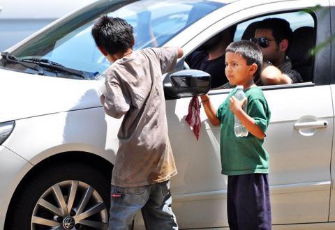Dos niños trabajando limpiando coches