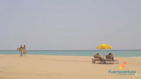 Playa de Fuerteventura con dos surferos y dos hamacas