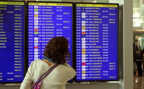 Una mujer delante de un panel informativo de un aeropuerto