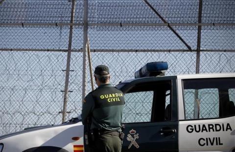 Un guardia civil de espalda en la valla de Melilla