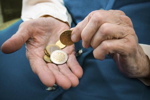 Monedas en la mano de un anciano