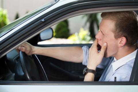 Un hombre bostezando en un coche
