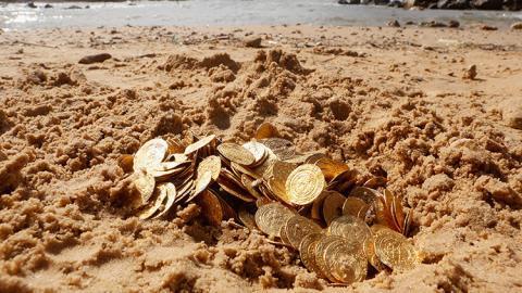 Monedas en la arena de una playa