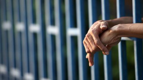manos entre los barrotes de una cárcel