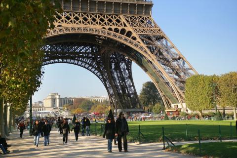 Personas paseando bajo la Torre Eiffel