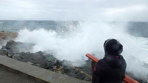 Una mujer mira al mar con olas
