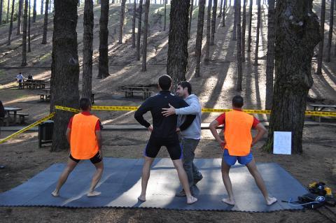 Fisioterapeuta con tres hombres haciendo ejercicios