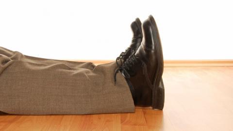Pies de un hombre desmayado en el suelo