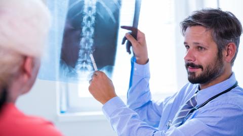 Médico con paciente enseñando radiografía
