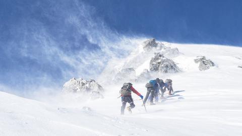 Tres hombres haciendo montañismo
