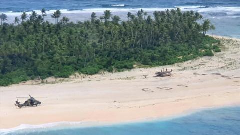 Señal de SOS en la playa de la isla Pikelot